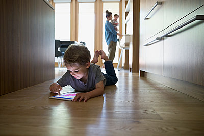 Boy laying and drawing on digital tablet on kitchen hardwood floor - p1192m1183914 by Hero Images