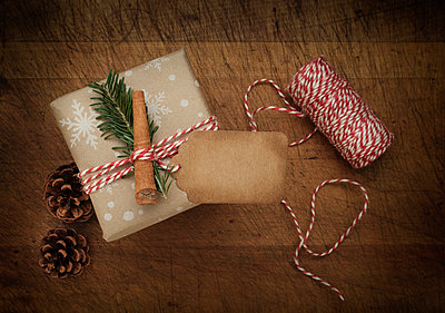 Carrot and pine frond tied to Christmas present - p1427m2163699 by Tetra Images