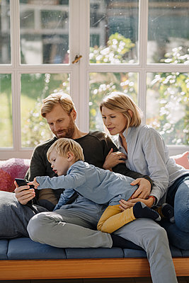 Family using cell phone in sunroom at home - p300m2205532 by Kniel Synnatzschke