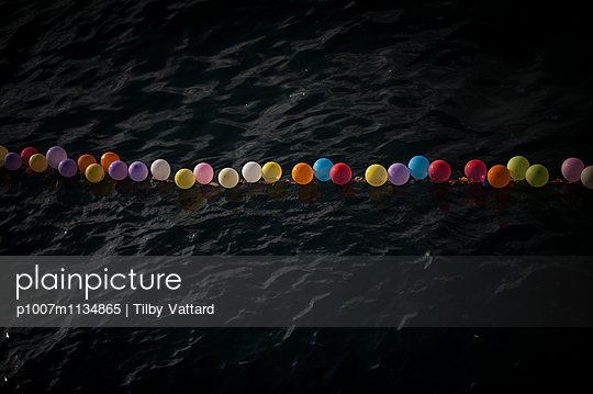 Color balloons in a dark water - p1007m1134865 by Tilby Vattard