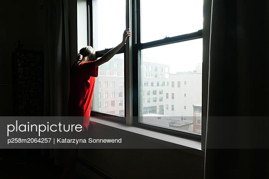 Woman at window - p258m2064257 von Katarzyna Sonnewend
