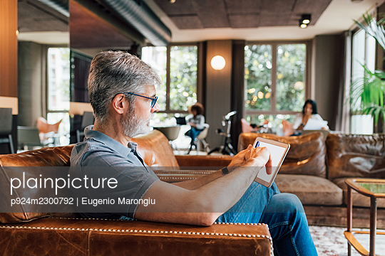 Italy, Man using digital tablet on sofa in creative studio - p924m2300792 by Eugenio Marongiu