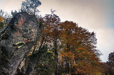 Man free climbing on steep face - p1352m1425333 by Kilian Reil