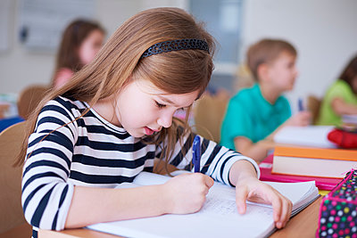 Schoolgirl writing in exercise book in class - p300m1587209 by gpointstudio