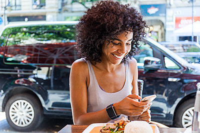 Portrait of smiling young woman with  sitting at pavement restarant looking at cell phone - p300m2030320 by Tom Chance