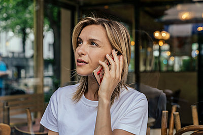 Portrait of woman on the phone in front of a coffee shop - p300m2199265 by Mareen Fischinger