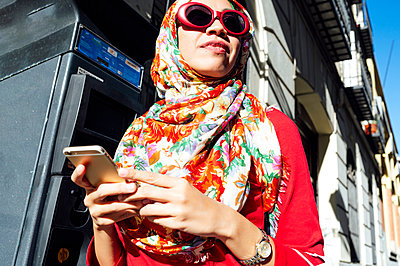 Woman in floral hijab looking away while holding mobile phone on sunny day - p300m2240874 by Jose Luis CARRASCOSA