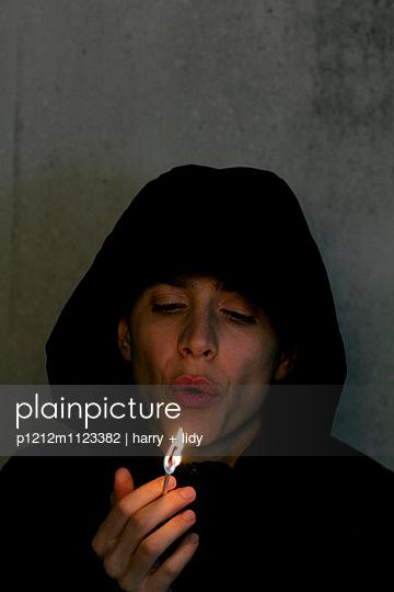 Kapuzenfrau pustet brennendes Streichholz aus - p1212m1123382 von harry + lidy