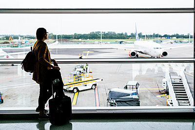 Full length side view of businesswoman looking through glass window at airport - p1264m1122102f by Astrakan
