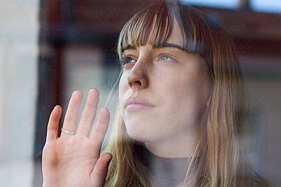 Attraktive, junge Frau mit Pony sieht durch ein Fenster und berührt dieses mit ihrer Handfläche  - p1301m2021004 von Delia Baum