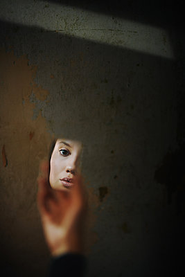 Woman reflected in the hand mirror - p1577m2220121 by zhenikeyev