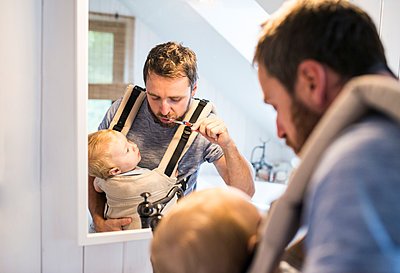 Father with baby in baby carrier brushing his teeth - p300m1205177 by HalfPoint