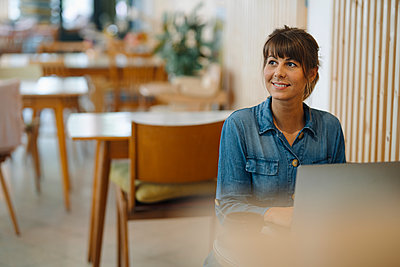 Businesswoman smiling while looking away using laptop sitting in coffee shop - p300m2226575 by Gustafsson