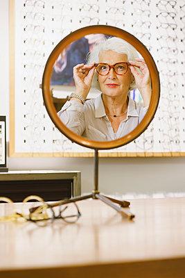 Portrait of senior woman wearing eyeglasses reflecting on mirror at store - p301m1498508 by Halfdark