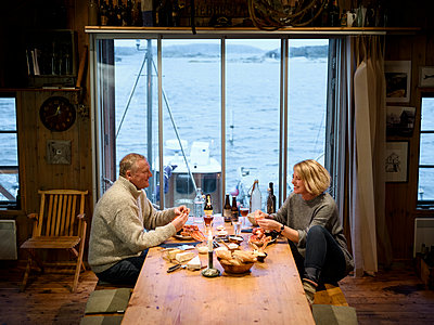 Mature couple having meal - p312m1063648f by Stefan Isaksson