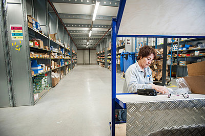 Female warehouse worker preparing orders on delivery trolley - p429m803054f by Arno Masse