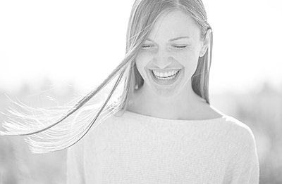 Laughing young woman with hair in the wind - p552m2214904 by Leander Hopf