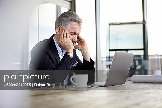 Businessman with headaches sitting at desk in office - p300m2012955 von Rainer Berg
