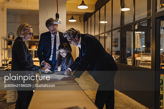 Business people and girl looking at shining tablet in office - p300m2156029 by Gustafsson