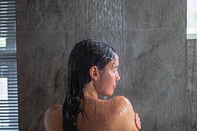 Young brunette woman taking a shower in a modern bathroom - p1315m2130782 by Wavebreak