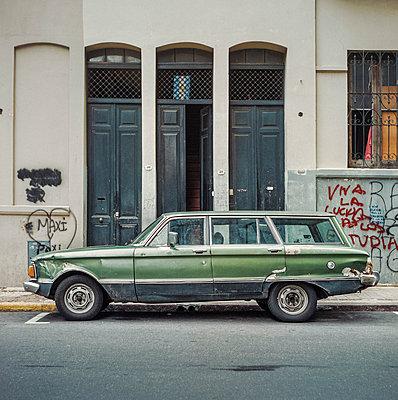 Ein grüner, argentinischer Ford Falcon, geparkt vor einem Haus in Buenos Aires mit hohen Holztüren und Graffiti an den Wänden - p1400m1516901 von Bastian Fischer