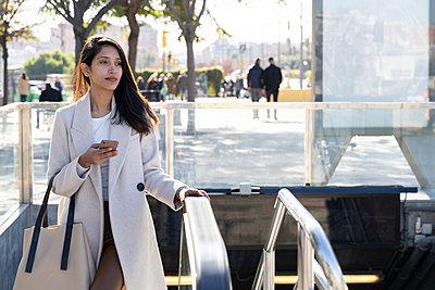 Young woman with smartphone leaving subway station - p300m2166214 by VITTA GALLERY