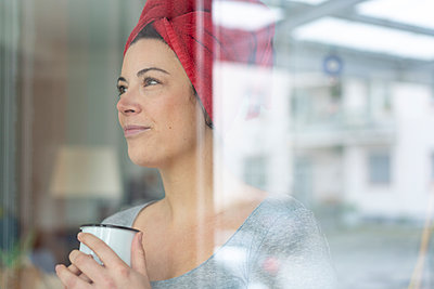 Portrait of woman with head wrapped in a towel drinking a coffee behind windowpane - p300m2171234 by Robijn Page
