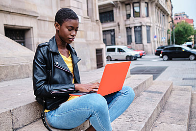 Young woman working on laptop while sitting in city - p300m2250220 by Alvaro Gonzalez