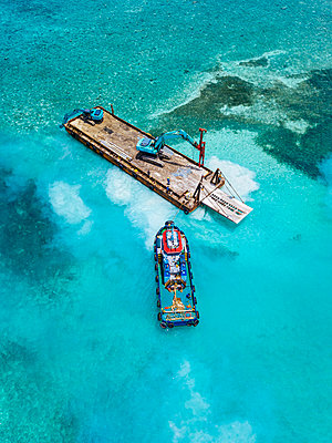 Aerial view of earth movers handling poles on floating platform in Male Atoll - p300m2275904 by Konstantin Trubavin