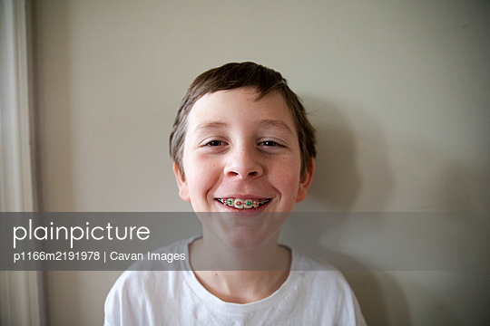 Tween Boy With Red and Green Braces Grins At Camera, Close Up - p1166m2191978 by Cavan Images