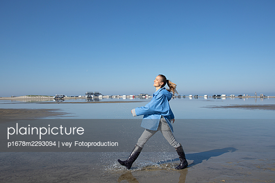 Woman taking a walk by the sea - p1678m2293094 by vey Fotoproduction