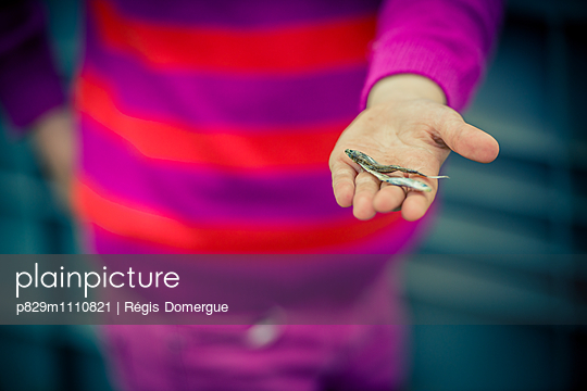 Mädchen hält kleinen Fisch in der Hand - p829m1110821 von Régis Domergue