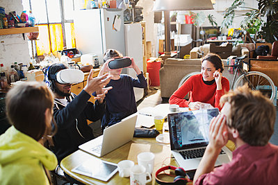 Young college student friends studying, using virtual reality simulator glasses at kitchen table in apartment - p1023m2024474 by Tom Merton