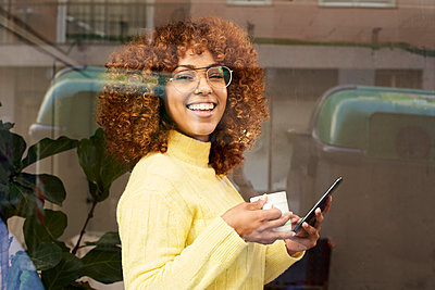 Happy woman holding mobile phone while having coffee in cafe - p300m2244152 by Veam