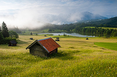 Germany, Bavaria, Werdenfelser Land, lake Geroldsee with hay barn at sunset, in background the Karwendel mountains - p300m911405f by Roy Jankowski