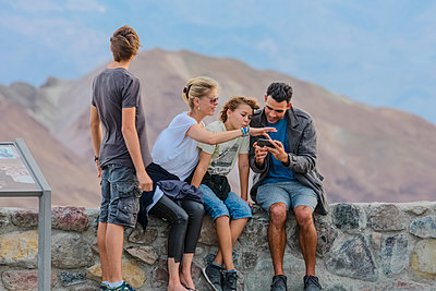 Family using cell phone at national park - p555m1409820 by Eric Raptosh Photography