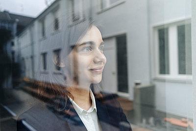 Frau blickt aus dem Fenster - p586m1492133 von Kniel Synnatzschke