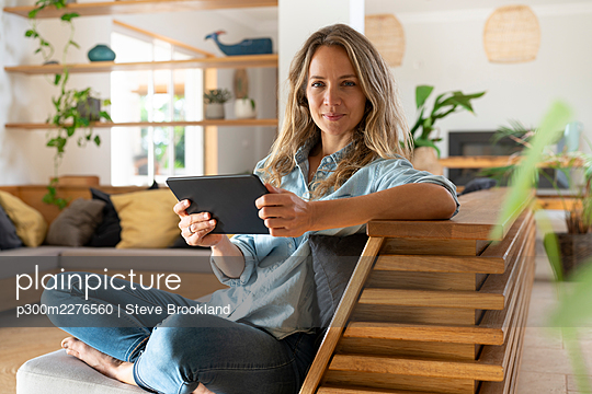 Happy woman holding tablet while sitting with legs crossed on couch in living room - p300m2276560 by Steve Brookland