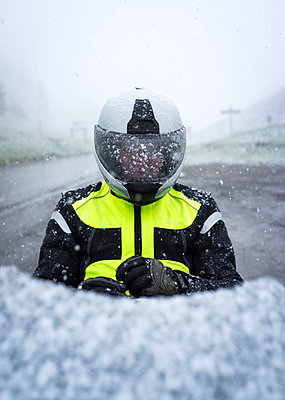 Snow covered motorcyclist sitting on motorcycle - p1053m793973 by Joern Rynio