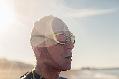 A swimmer in a wet suit, swimming hat and goggles on a beach.  - p1100m1112334f by Mint Images