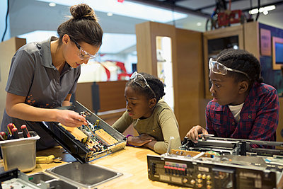 Scientist teaching twin sisters assembling electronics in science center - p1192m1194254 by Hero Images