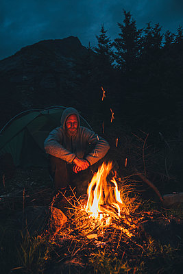 Norway, Lofoten, Moskenesoy, Young man sitting at camp fire - p300m2005594 von Gustafsson