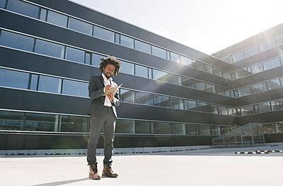 Businessman taking notes outside office - p300m2113996 von Hernandez and Sorokina