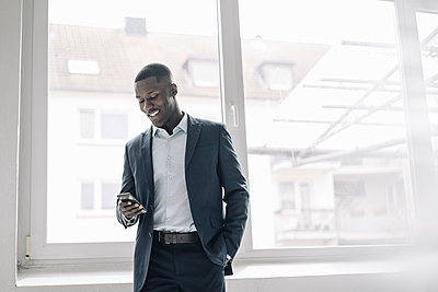 Portrait of smiling young businessman standing in front of window looking at cell phone - p300m2166756 von Kniel Synnatzschke