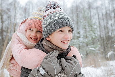 Portait of boy giving his little sister a piggyback ride in winter forest - p300m2166999 by Ekaterina Yakunina
