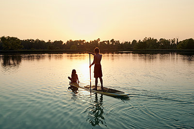 Caucasian boy and girl on paddleboard on lake - p555m1479670 by King Lawrence