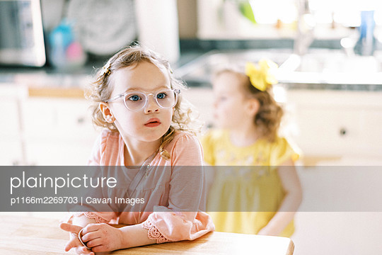 Little twin girl with glasses looking on sitting at kitchen table - p1166m2269703 by Cavan Images