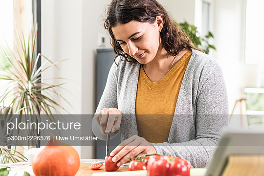 Woman cutting vegetable while sitting by table at home - p300m2226576 by Uwe Umstätter