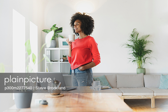 Woman holding coffee cup while standing in living room - p300m2277540 by Steve Brookland