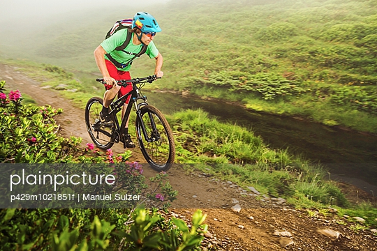Young male mountain biker cycling next to stream - p429m1021851f by Manuel Sulzer